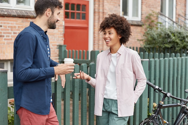 Positive multiracial couple walk in rural setting, stroll during weekends, drink takeaway coffee, stand near fence, have pleasant talk with each other