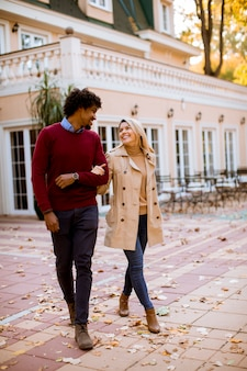 Positive multiracial couple walk on the street at autumn