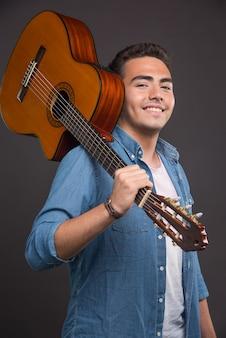 Positive musician holding guitar on black background