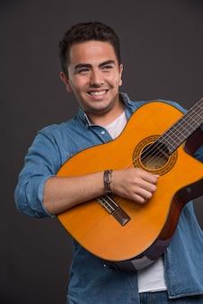 Позитивный музыкант, играющий на гитаре на черном фоне