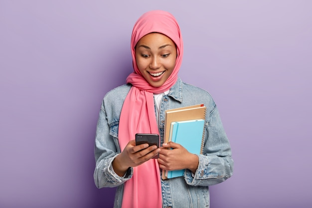 Positive muslim female looks at smatphone device, wears pink hijab, denim jacket