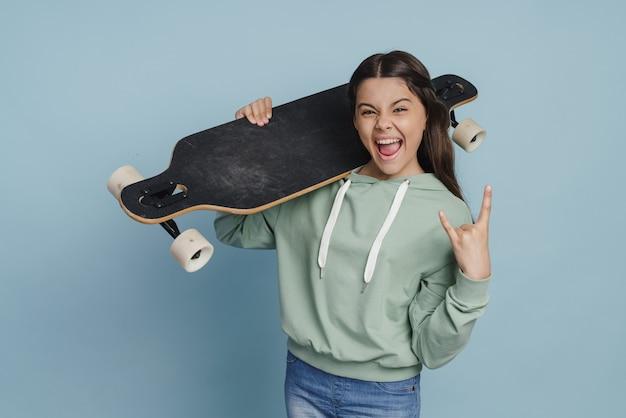Позитивная, непослушная девушка держит конек на плече, показывая рок-жест. девушка-подросток, изолированные на синем фоне Premium Фотографии