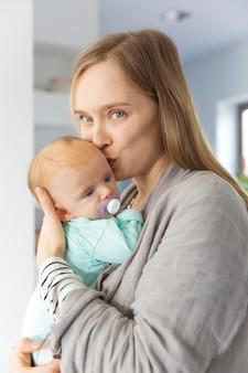 Новая позитивная мама целует и обнимает малыша