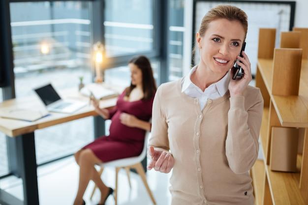 ポジティブなニュース。笑顔の秘書が携帯電話で話し、同僚が椅子に座ってリラックスしながら目をそらしている