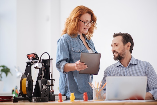Positive nice cheerful man sitting at the laptop and looking at his colleague while talking with her