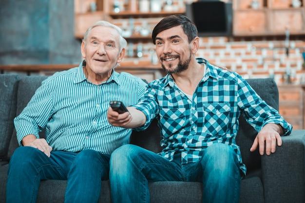 긍정적 인 좋은 기쁘게 아버지와 아들이 함께 앉아 집에서 쉬고있는 동안 tv를보고