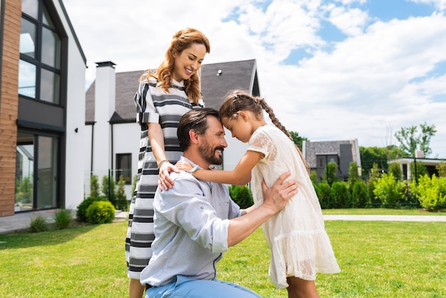 Positive nice girl looking at her father while standing on the lawn in front of their house