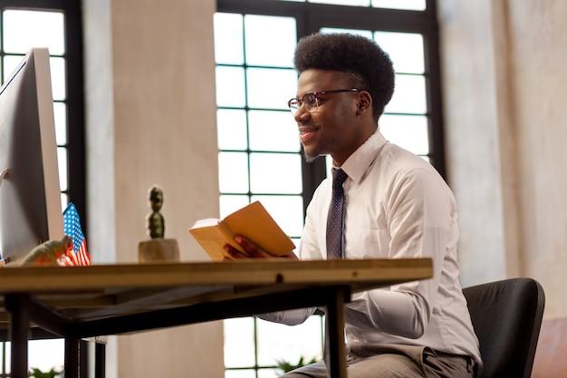 彼の手で彼のノートを持って笑っているポジティブなナイスマン