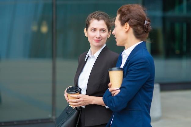 屋外で一緒に歩く、話している、プロジェクトについて話し合っている、またはチャットしているテイクアウトのコーヒーカップを持つ肯定的なオフィスの女性の友人。ミディアムショット。休憩コンセプト