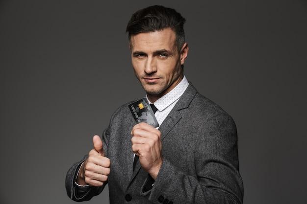 Позитивный офисный мужчина в строгом костюме и галстуке демонстрирует цифровые деньги в пластиковой кредитной карте и показывает палец вверх, изолированный над серой стеной