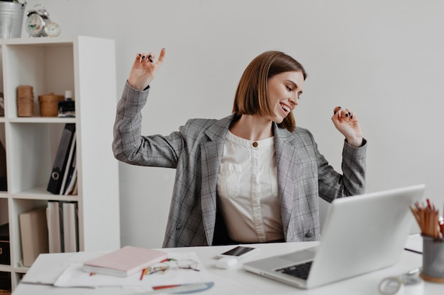 Positive office worker in white shirt dancing while sitting at table on of shelves with documents.