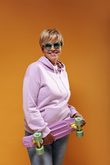 Positive old lady with blonde hair and trendy sunglasses in pink fashionable sweatshirt and cool jeans smiling and holding skateboard.