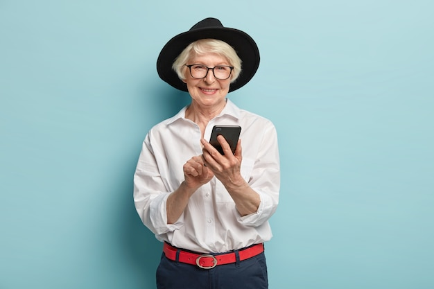 Positiva signora anziana con la faccia rugosa, felice finalmente di imparare a usare smartphone e internet, indossa occhiali trasparenti, cappello nero, camicia e pantaloni eleganti, isolati sopra il muro blu.