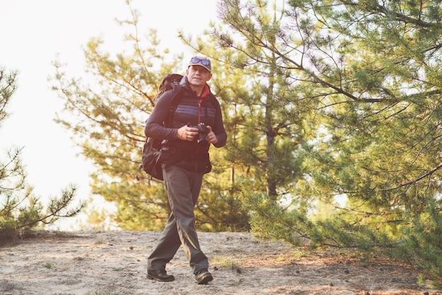 Позитивный старик фотографирует пейзаж в лесу