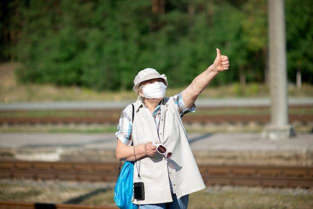 医療用フェイスマスク、帽子、写真カメラを持つポジティブな老婆