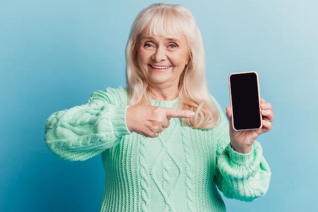 긍정적인 노파는 파란색 배경에 격리된 스마트폰 포인트 손가락 터치 스크린을 들고 있습니다.