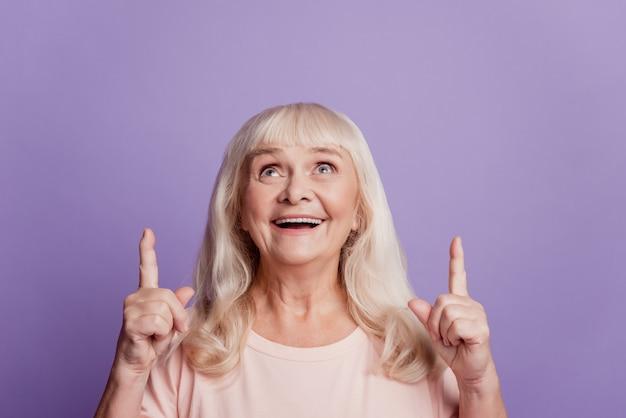 보라색 배경 위에 격리된 카피스페이스를 가리키는 긍정적인 노부인 검지 손가락