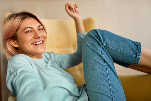 Позитивный oprimistic очаровательная молодая женщина с кольцом в носу смеется, отдыхая дома на выходных