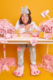 Positive optimistic brunette asian woman in nightwear works at office desk surrounded by cut paper points away eats delicious cornflakes isolated over yellow wall