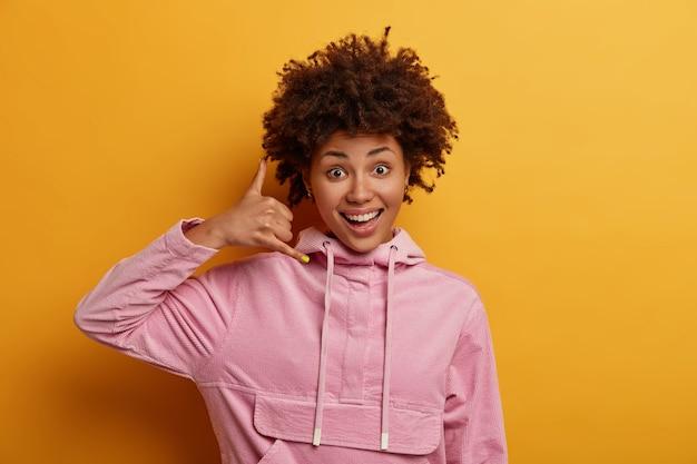 ポジティブな楽観的な縮れ毛の千年紀の女性は、電話のジェスチャーをし、私に電話をかけ直し、電話番号を尋ね、楽しく笑い、カジュアルなパーカーを着ています。接続通信の概念