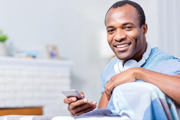 Позитивный оптимистичный приятный мужчина смотрит на вас и улыбается, держа свой смартфон