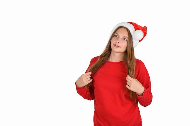 Позитивно-оптимистичная симпатичная женщина в повседневном красном свитере и шляпе санта-клауса, мечтательно ожидая рождества