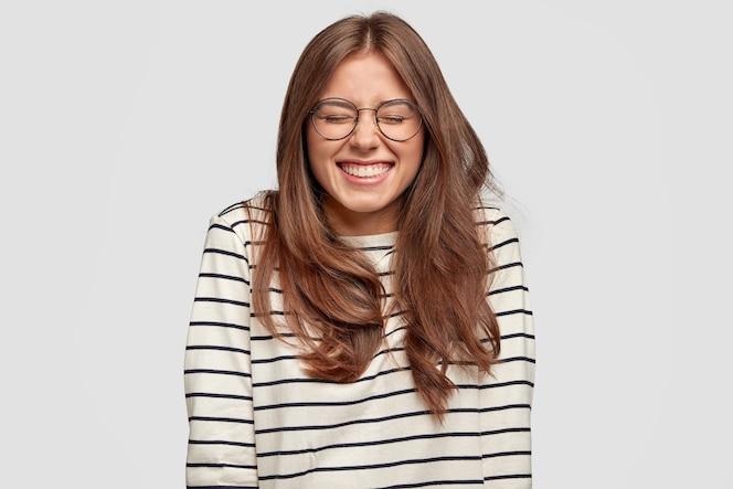 Позитивная, оптимистичная молодая женщина радостно улыбается, у нее белые ровные зубы, небрежно одета, в приподнятом настроении, выражает счастье, проводит свободное время с друзьями, изолированно за белой стеной
