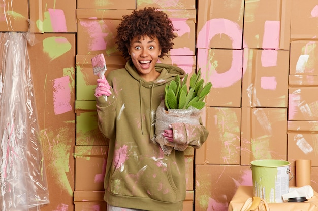 Positive overjoyed dirty woman holds cactus in pot and paint brush has dirty clothes after painting walls in room surrounded by paint buckets. people renovation and home improvement concept.