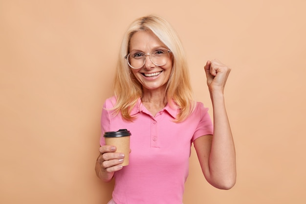 Positive overjoyed fair haired middle aged european woman clenches fist celebrates success drinks takeaway coffee wears big optical glasses casual pink t shirt isolated over beige wall