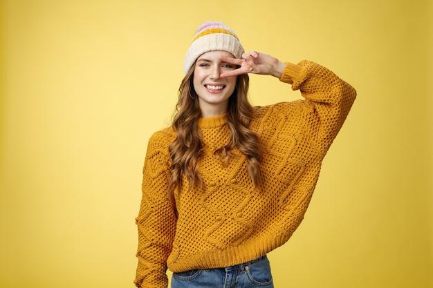Positivo pacifico gentile affascinante giovane donna mostra pace gesto di vittoria vicino all'occhio sorridente largamente buon umore giorno perfetto augurandoti buona fortuna, in piedi allegro ghignante sfondo giallo