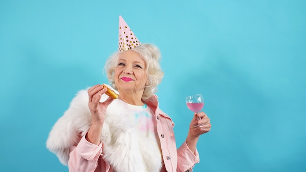 Positive pensioner with a cap on her head poses . the concept of birthday.