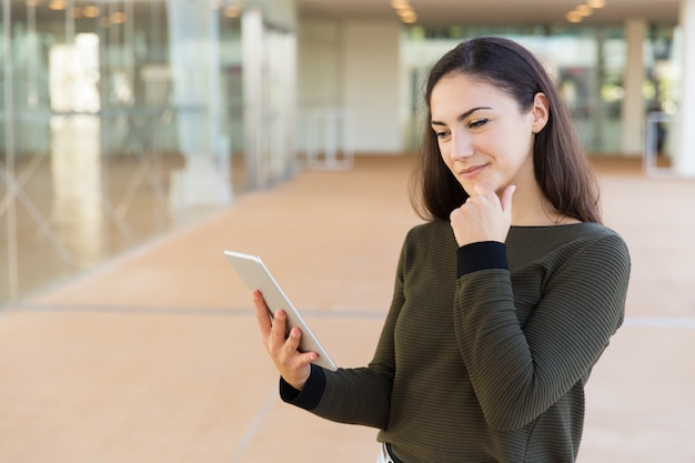 Positive pensive female customer reading message