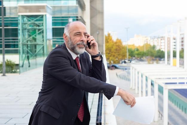 携帯電話で話している肯定的な物思いに沈んだ灰色の髪の実業家