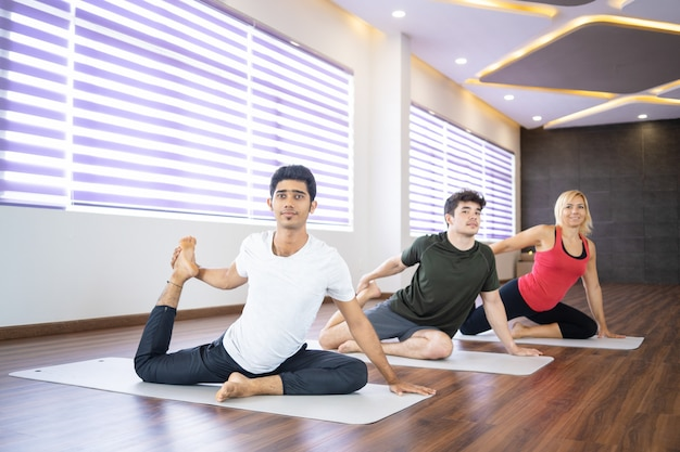 Positive people doing mermaid pose at yoga class