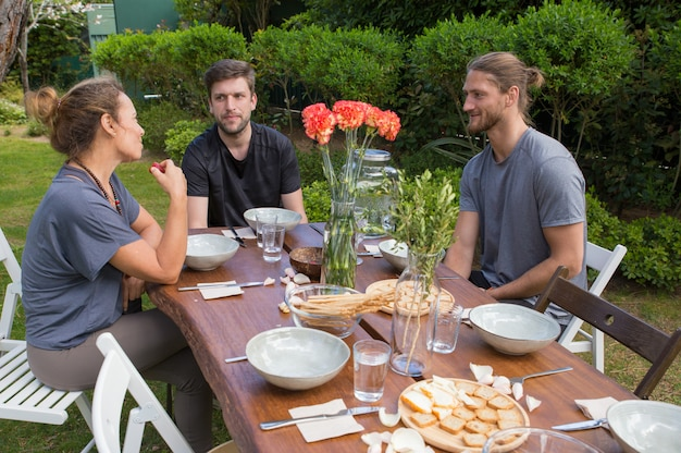 Positive people having meal at wooden table in backyard