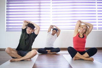 Positive people stretching arms at yoga class