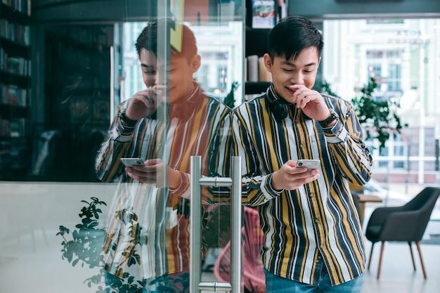 Позитивный человек, стоящий возле стеклянной двери и касающийся своего носа, глядя на экран смартфона
