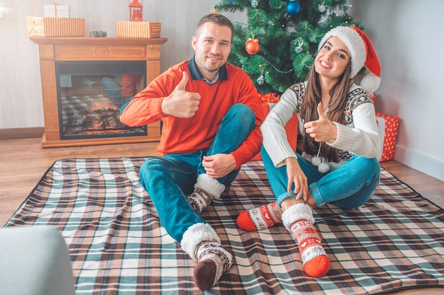 Positive picture of young couple sitting on blanket on floor