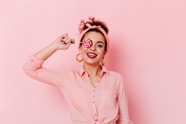 Positive pin-up girl with red lipstick in pink outfit and gold earrings holding lollipop.