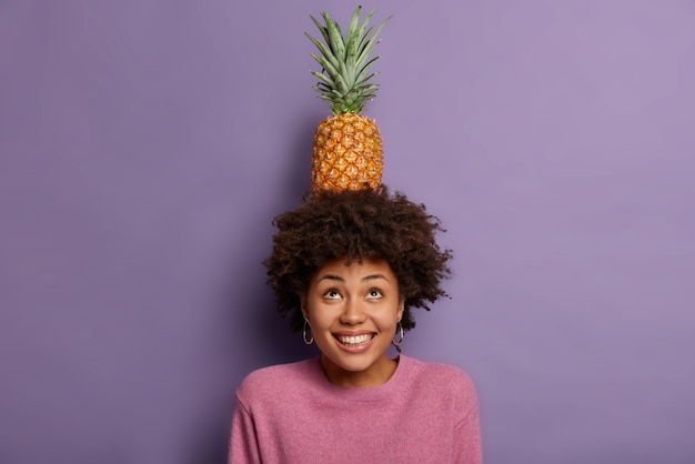 Positive playful adult woman looks above, fooling around