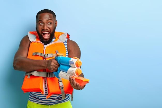 Позитивный игривый бородатый мускулистый мужчина позирует с пляжными предметами