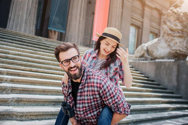 Positive and playful couple stand on stairs. young man holds woman on back and smile. she looks down. theyspend time together.