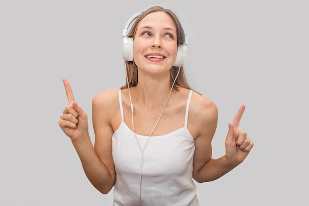 Positive and playful young woman listening to music through white headphones.