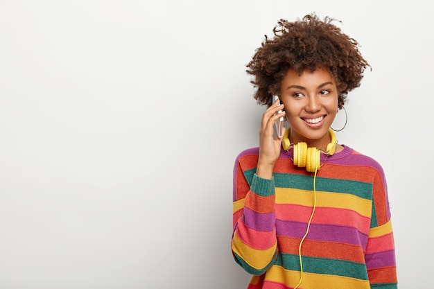 Positive pleasant looking curly woman has casual phone talk, enjoys communication, dressed in casual outfit, uses headphones for listening audio tracks