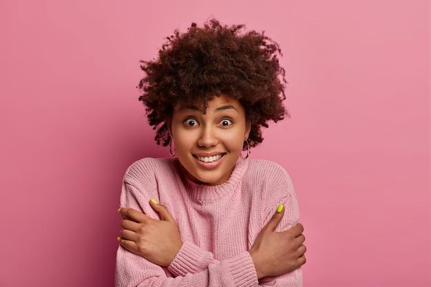 ポジティブで見栄えの良い女性は、体に腕を組んで、寒さから震え、歯をガタガタと鳴らし、暖かい服装を必要とし、喜んで見え、バラ色のパステルカラーの壁に向かってポーズをとります。いや、なんて肌寒い!