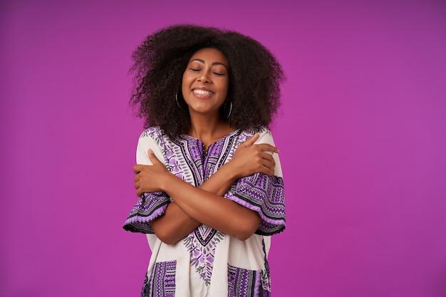 紫にポーズをとって、抱き締めて、目を閉じて真摯に笑うカジュアルな髪型のポジティブで心地よい若い暗い肌の女性