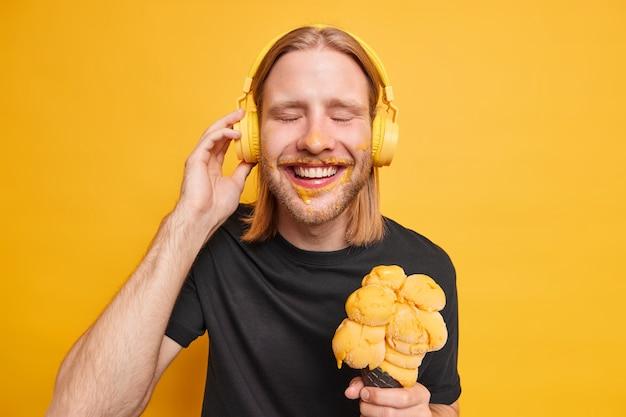 Позитивный довольный рыжий парень закрывает глаза и счастливо улыбается, наслаждается любимой песней, держит руку в наушниках, держит большое вкусное мороженое, имеет свободное время в выходной день летом, изолирован на желтой стене