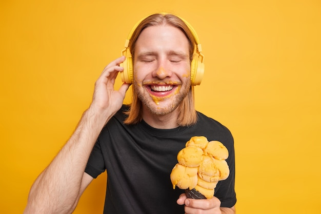 Il ragazzo rosso soddisfatto positivo chiude gli occhi e sorride felicemente gode della canzone preferita tiene la mano sulle cuffie tiene un grande gelato gustoso ha tempo libero durante il giorno libero in estate isolato sul muro giallo