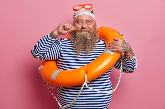 긍정적 인 통통한 남자 컬 콧수염은 수영 고글과 줄무늬 선원 셔츠를 착용하고 해변에서 안전 장비와 함께 포즈를 취하고 여름 휴가를 즐깁니다. 휴식과 계절 개념