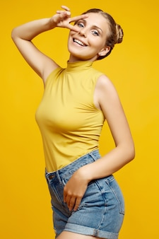Positive portrait of gorgeous blonde hipster woman model with curly hair posing on colorful yellow background in studio